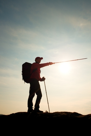 tourist guide: Tourist guide show the right way with pole in hand. Hiker with sporty backpack stand on rocky view point above misty valley. Sunny spring daybreak in rocky mountains.
