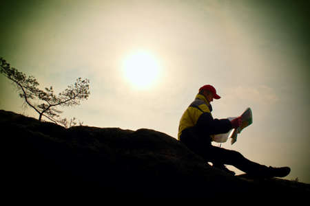 Silhouette of young tourist guide looking in paper map in nature while hiking Reklamní fotografie