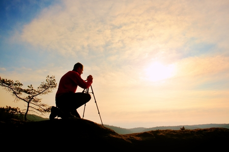 Nature photographer with tripod on cliff and thinking. Dreamy fogy landscape, orange misty sunrise in a beautiful valley below Reklamní fotografie
