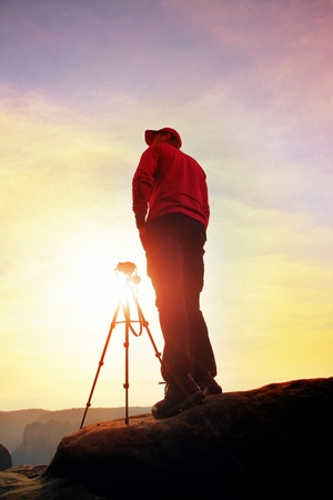 Photographer stay with tripod on cliff and thinking. Dreamy fogy landscape, orange misty sunrise in a beautiful valley below