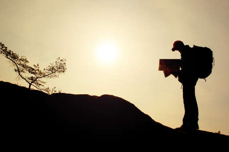 tourist guide: Silhouette of young tourist guide looking in paper  map in nature while hiking Stock Photo