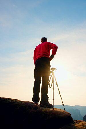 rocky peak: Photographer takes photos with camera on tripod on rocky peak. Dreamy spring in rocks. Stock Photo