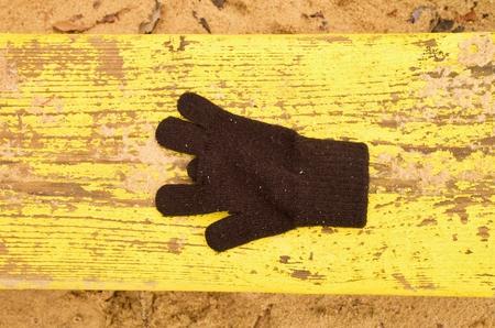 jardin de infantes: Perdido guantes de lana en el banco amarillo. banco de madera de arena. Caj�n de arena con arena sucia en el jard�n de ni�os. Banco de madera. Foto de archivo