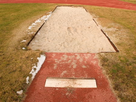 salto de longitud: Lane por el salto de longitud. Retractarse de arena de color rojo, blanco placa aga-off. La mala hierba alrededor.