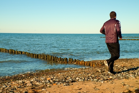 vignetting: Tall man in dark sportswer running and exercising on stony beach at breakwater. Vivid and vignetting effect