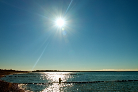 pers: Fisher with rod in golden sunshine with beautiful sea. Fishing at breakwaters in cold Baltic sea