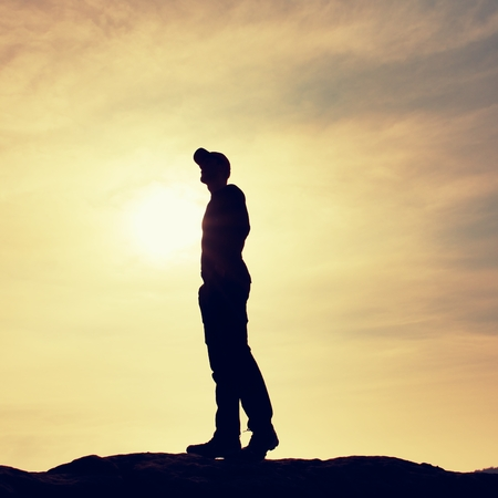 conceited: Silhouette human standing on rocky pedestal on nature daybreak  background. Strong sun. Stock Photo