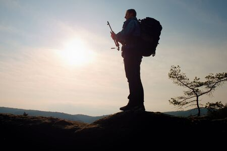 folding camera: Alone adult photographer folding tripod with camera. Man  at sunrise at open view on mountain peak, blue sky