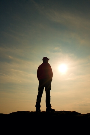 Silhouette human standing on rocky pedestal on nature daybreak  background. Strong sun. Stock Photo