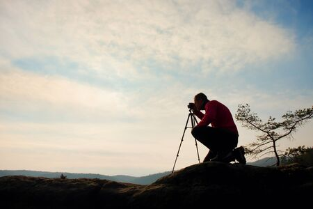 Amateur photographer takes photos with mirror camera on peak of rock. Dreamy fogy landscape, spring orange pink misty sunrise in a beautiful valley below