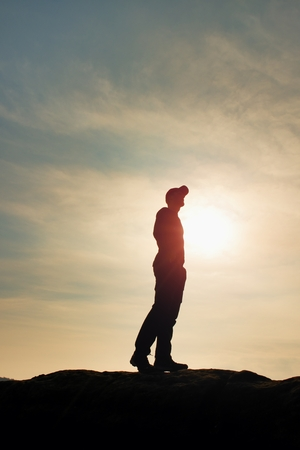 presumptuous: Silhouette human standing on rocky pedestal on nature daybreak  background. Strong sun. Stock Photo