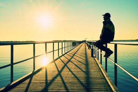 warm jacket: Man in warm jacket and baseball cap sit on pier handrail construction and enjoy morning at sea. Sunny clear blue sky, smooth water level