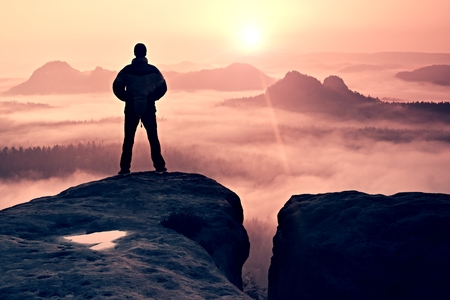 Man on peak of sandstone rock in national park Saxony Switzerland watching to Sun. Beautiful moment the miracle of nature