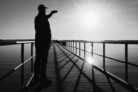 port everglades: Man on pier photograph morning sea. Tourist with smart phone in hand. Fantastic morning with  smooth water level