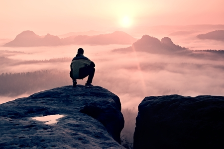 Man on peak of sandstone rock in national park Saxony Switzerland watching to Sun. Beautiful moment the miracle of nature Stock Photo