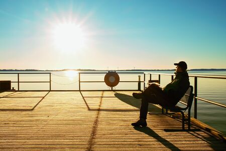 port everglades: Tourist sit on wharf construction and enjoy morning at sea. Sunny clear blue sky, smooth water level Stock Photo