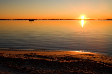 rising dead: Smooth lake level at warm colorful  sunset, sandy beach in bay