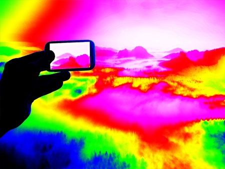 thermography: Fantastic infrared scan. Tourist hand takes photos by smartphone on view point and watching into misty spring valley.  Thermography colors.
