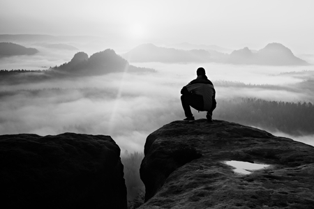 Man on peak of sandstone rock in national park Saxony Switzerland watching to Sun. Beautiful moment the miracle of nature Reklamní fotografie