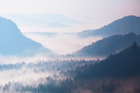 Inicio de la primavera. amanecer de ensueño fantástico por encima de profundo valle escondido en las montañas rocosas. Hermosa primavera día brumoso