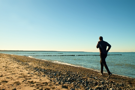 tall man: Tall man in dark sportswer running and exercising on stony beach at breakwater. Vivid and vignetting effect