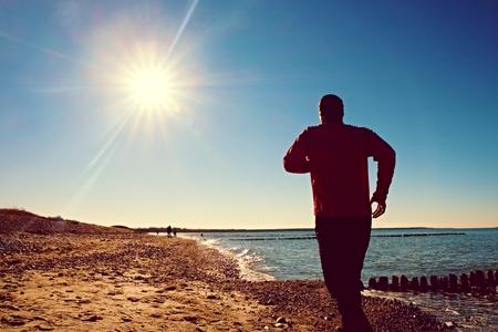 persona saltando: hombre alto en el funcionamiento sportswer oscuro y el ejercicio en la playa pedregosa en el rompeolas. efecto vivo y las viñetas