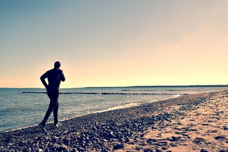 Silhouette de grand homme dans la course noire et de l'exercice sur la plage caillouteuse au brise-lames. effet de vignettage Vivid et fort