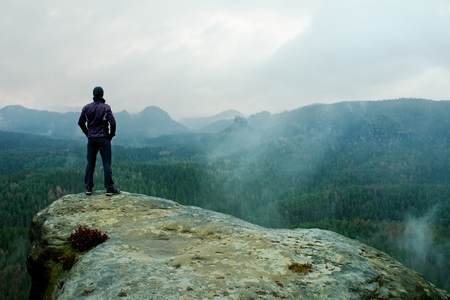 empires: Hiker on sharp cliff of sandstone rock in rock empires park and watching over misty and foggy Spring Valley