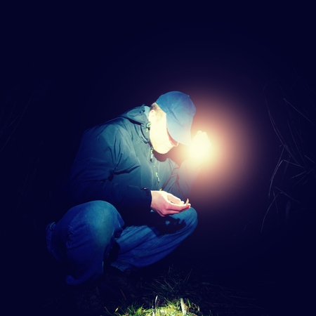 finger proof: Adult man in blue wearing sit and looking for something in wet grass with light in hand , scary or fairytale night Stock Photo