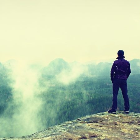 empires: Hiker is standing on sharp cliff of sandstone rock in rock empires park and watching over the misty and foggy spring valley to Horizon.