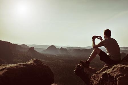 пейзаж: Турист в серой футболке принимает фотографии с смарт-телефон на вершине скалы. Мечтательный холмистый пейзаж ниже, весной туманное восход солнца Фото со стока