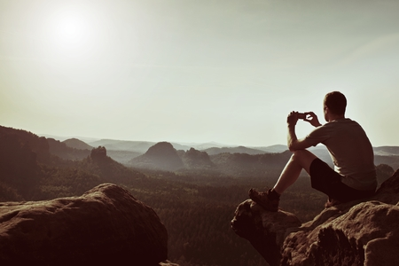 Tourist in gray t-shirt Takes photos with smart phone on the peak of rock. Dreamy hilly landscape below, spring misty sunrise