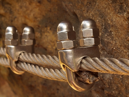 solid wire: Solid knot on steel rope. Iron twisted rope fixed in the block by strong screws snap hooks. Detail of rope end anchored into rock wall Stock Photo