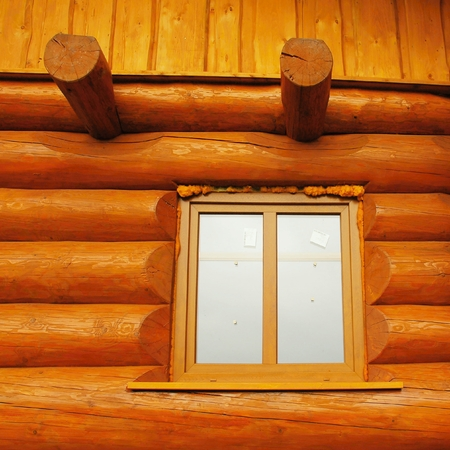 fungicide: Detail of window built in wooden beams cabin wall. Painted wood with fungicide light red paint.