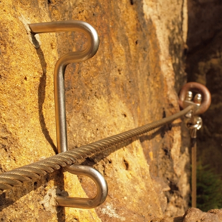 crack climb: Rock climbing safety path via ferrata. Steel chrome anchored in rock tribute steel rope