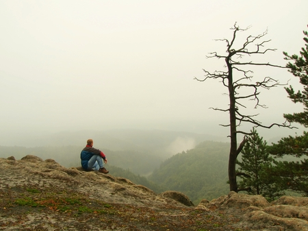 melancholy: Melancholy and sad day. Man at cliff of rock above deep vally. Tourist on the peak of sandstone rock watching into the misty landscape.