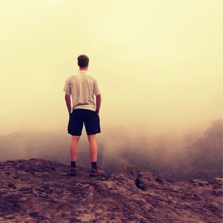 pantalones abajo: Caminante edad en una camisa gris y pantalones oscuros. hombre alto en la cima de una roca arenisca mirando hacia abajo este paisaje. efecto de fotografía antigua.