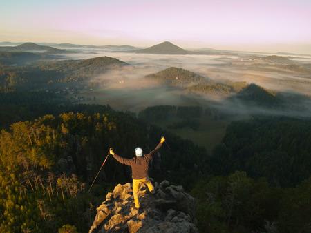 apuesto joven sentado en la roca y disfrutar de la vista en las montañas brumosas Rocosas. Foto de archivo