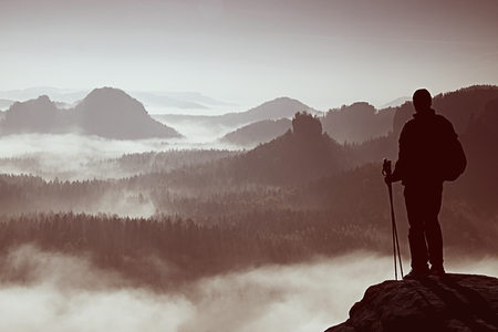 rocky point: Silhouette of tourist with poles in hand. Sunny spring daybreak in the Rocky Mountains. Hiker with sports backpack stand on rocky view point above the misty valley. Stock Photo