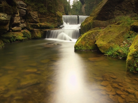weir: Stony weir on the small mountain river. Stream is flowing over sandstone blocks and makes milky water. Stock Photo