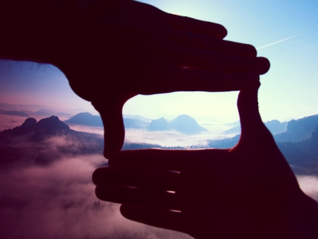 rocky peak: Close up of hands making frame gesture. Blue misty valley bellow rocky peak. Sunny spring daybreak in mountains.