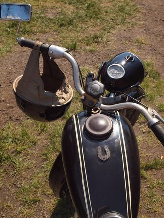 he is public: Handlebars with mirror and vintage motorcycle helmet he made in the sixtieth. Czech public motorcycle on The old timer show.