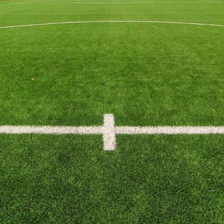 soccer net: Orange plastic hanger in aluminum field in soccer gate, black football soccer net. Light green grass on football playground in the background