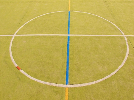 bounds: Empty outdoor handball playground, plastic light green surface on ground white and blue bounds lines.
