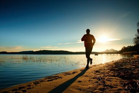 スポーツ アクティブな大人の男を実行していると、ビーチで運動のシルエット。島、夕焼けの空を背景に穏やかな水。