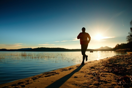 Silhouette of sport active adult man running and exercising on the beach. Calm water, island and sunset sky background.