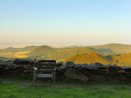 broken hill: View from hill over rest place with old wooden chair down to countryside. Spring morning on the peak of hill.