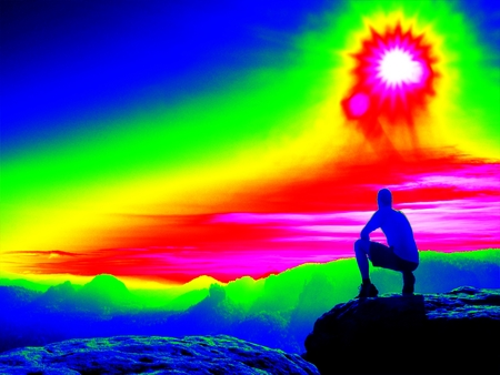 thermography: Man on rock. Fantastic infrared scan. Tourist on the rocky peak. Daybreak in mountains, heavy mist in deep valley in colors of ultra violet measurement