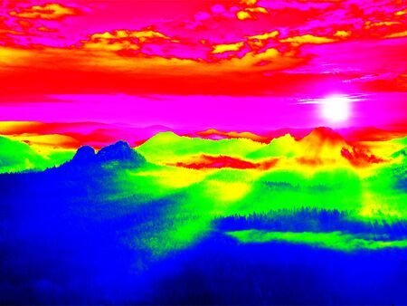 thermography: Infrared scan of rocky landscape, pine forest with colorful fog, hot sunny sky above. Grunge background in amazing thermography colors. Stock Photo