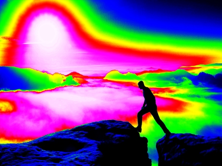 gamma radiation: Man on rock. Fantastic infrared scan. Tourist on the rocky peak. Daybreak in mountains, heavy mist in deep valley in colors of ultra violet measurement